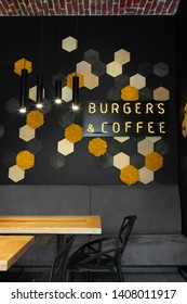 Interior of cafe . Loft space design, . creative minimalistic cafe interior, simplicity and geometry concept, black and yellow colors.Creative space. Decorative honey cell with color moss on the wall.
