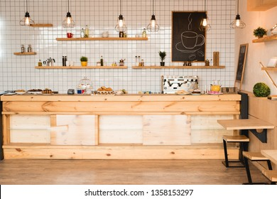 interior of cafeteria with wooden bar counter, shelves and board with drawn coffee cup