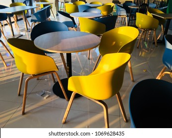 Interior of canteen area with blue and yellow plastic chair and wood table.