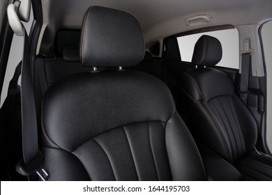 the interior of the car is covered with handmade genuine leather. front car seats. top. head restraints and seat belts are visible. High-quality stitching with gold threads and skin texture are visibl - Shutterstock ID 1644195703