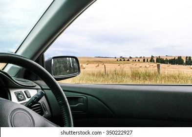 Interior of car with steering wheel and country side of paddocks with hay bails visible out of window and trees in rear vision mirror. Drive in the country.
