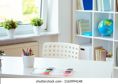 Interior of child room with white table and colorful pencils on him and shelf with books on background