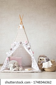 Interior of a children's room with soft toys. Children's Tent with toys bunnies, a pillow, decorated with a garland.
