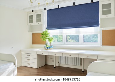 Interior of children's room for two children in light colors. White furniture, table, blue roman blind on the window