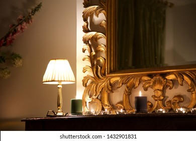 Interior: a chimney breast, upper mantle and decorative gilt mirror lit by the warm glow of a small side light with fabric shade and candles