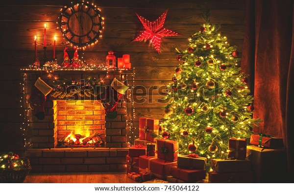 interior christmas. magic glowing tree, fireplace gifts in  dark at night