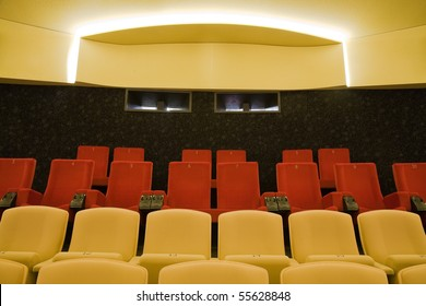 Interior of cinema auditorium with lines of red and sand color chairs.