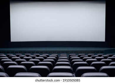 Interior cinema hall with white screen and black comfortable chairs. Concept of empty cinema hall.