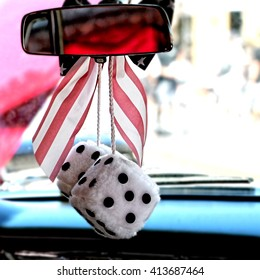 Interior of a classic car with fuzzy dice on the rear view mirror