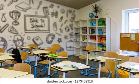 Interior of classroom in the modern school. School board, desks, textbooks. Back to school