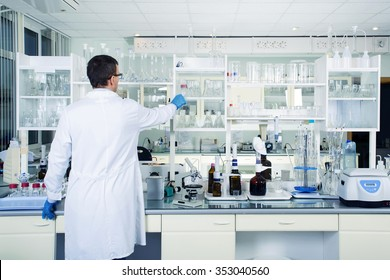 Interior of clean modern white medical or chemical laboratory background. Laboratory concept with caucasian male chemist. Horizontal template for a poster, webpage or leaflet.