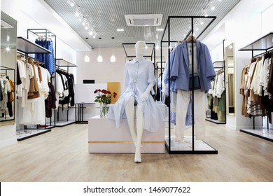 Interior of clothing store .Bright interior.Minimalistic style.Clothes hang on hanger.Trendy colors.