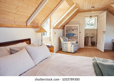 Interior of a comfortable master bedroom with an en suite bathroom in the loft of a contemporary residential home
