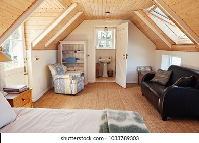 Interior of a comfortable master bedroom in the loft of a contemporary residential home with an en suite bathroom