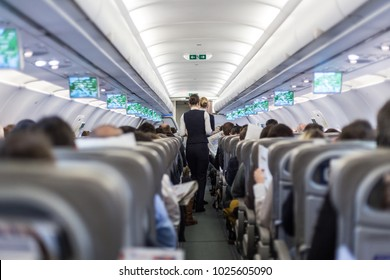 Interior of commercial airplane with flight attandant serving passengers on seats during flight. Stewardess in dark blue uniform walking the aisle. Horizontal composition.