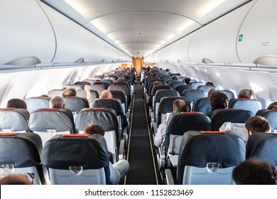 Interior of commercial airplane with unrecognizable passengers on their seats during flight shot from the rear of airplane.