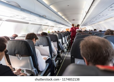 Interior of commercial airplane with unrecognizable passengers on their seats during flight. Stewardess in red uniform walking the aisle of commercial airplane.