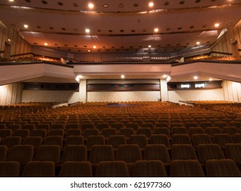 Interior of a concert hall or theater with light and velvet chairs