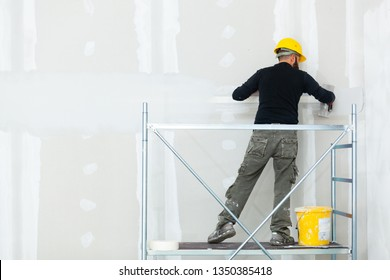Interior construction, worker plastering gypsum board wall.