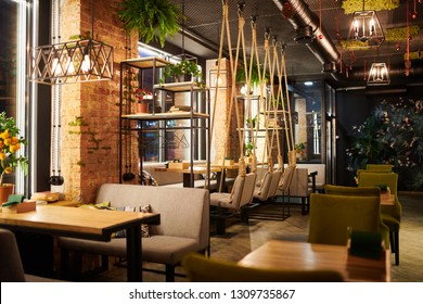 Interior of contemporary cozy cafe with several wooden tables, chairs and sofas prepared for guests