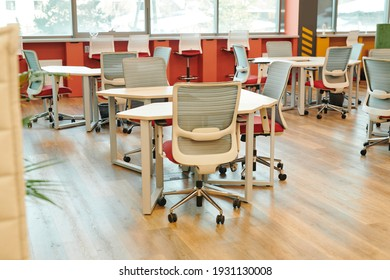 Interior of contemporary large open space office with many chairs by tables and along windowsills with no workers or managers around