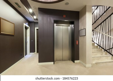 Interior of a corridor with passenger lift and marble stairs