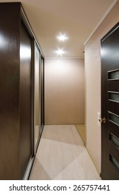 Interior corridor with wooden floors and artificial lighting