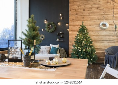 The interior of a country house is decorated with a Christmas tree in anticipation of the holiday. a large spacious light room is decorated with wood. the table is festively served