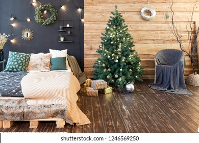 The interior of a country house is decorated with a Christmas tree in anticipation of the holiday. a large spacious light room is decorated with wood