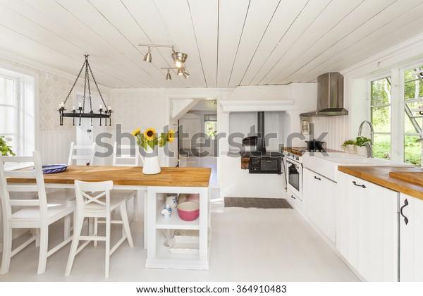 interior de una casa de campo con girasoles en la mesa y una antigua estufa de época