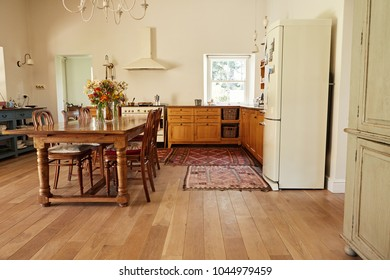 Interior of a country style kitchen in a bright residental home with a dining table, chairs and appliances