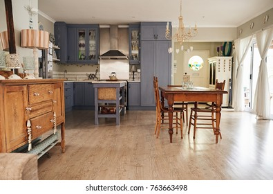 Interior of a country style kitchen in a residental home with an island, dining table and modern appliances