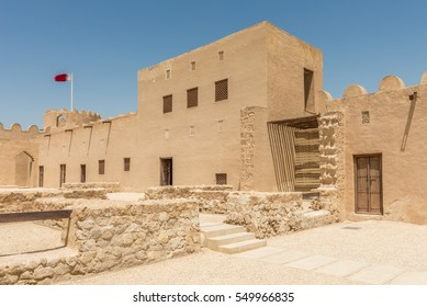 Interior courtyard of Riffa Fort, Bahrain on a sunny day with the Bahrain flag flying.