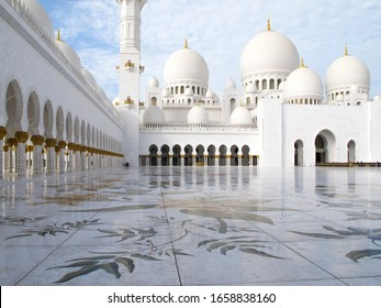 The interior courtyard of the Sheikh Zayed Grand Mosque, featuring domes, minarets and a marble floor.  It is the largest mosque in the country, and the key place of worship for daily, Friday and Eid.