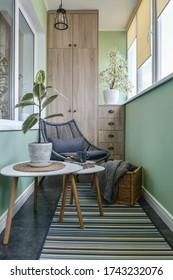 Innenausstattung des gemütlichen Balkons mit grünen Wänden, Sitzecke mit Teppich, Sessel und zwei Couchtischen