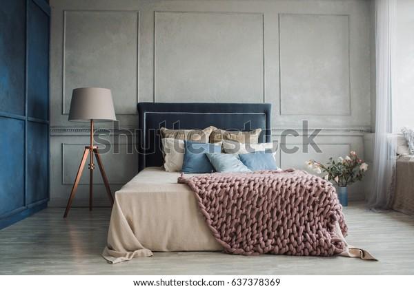 Interior of cozy bedroom in modern design with craft floor lamp