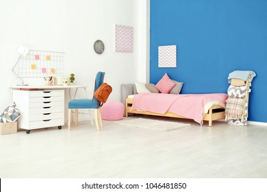 Interior of cozy children's room with table and comfortable bed