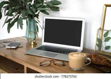 Interior of a cozy feminine home office with laptop mock-up, eucalyptus plant in vase, glasses, coffee cup, phone and frames. Styled blogger's workplace