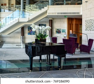 Interior of a cozy hotel lobby in stylish design. Nice black grand piano, vinous-violet chairs, marble floors, stairs. Modern place for relax in a luxury Hilton Hotel in Sofia, Bulgaria - June 6, 2017