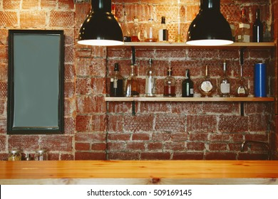 Interior of cozy pub or coffee shop or cafe with bottles of spirits on shelves, clean table, empty slate frames for text. Background