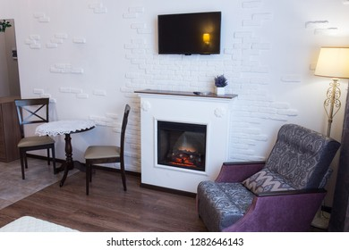 Interior cozy room with a fireplace where you can relax after hard work in the chair