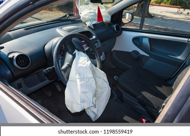 Interior of crashed car after accident with deflated airbags on road in city, sunny day