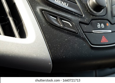 The interior dashboard of a car is building up dust, dirt, and debris.