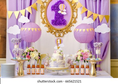 Interior decoration for a kids child birthday is one year in ultra violet trend year purple color. Candy, macaroon, tiered cake, and juices balloon. Anniversary dating one celebration.