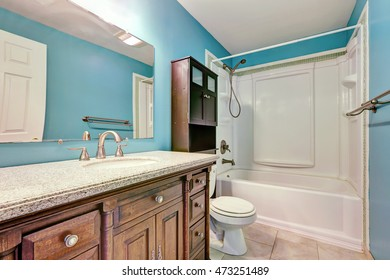 Interior design of blue bathroom in apartment. Wooden bathroom vanity with drawers and granite counter top. Northwest, USA