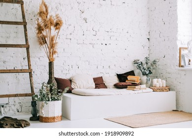 Interior design of bright living room with white walls and couch bench with pillows. Dried high plants and wooden ladder near wall.