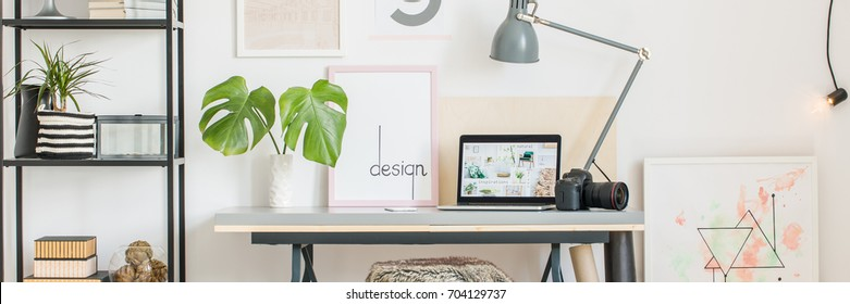 Interior design of creative home office in white scandi style, desk, laptop, camera, monstera, lamp and posters
