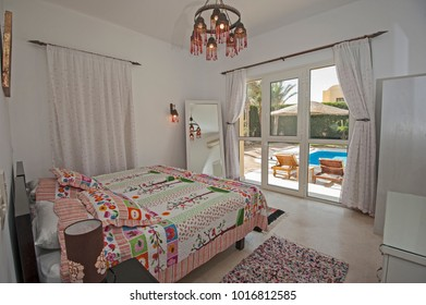 Interior design decor furnishing of luxury show home tropical villa bedroom with furniture and garden swimming pool view window