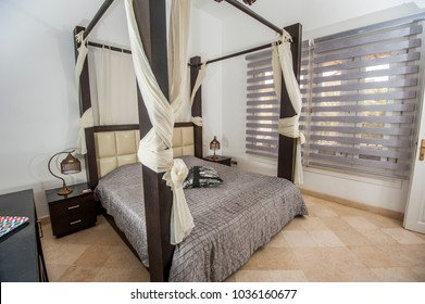 Interior design decor furnishing of luxury show home holiday villa bedroom with four poster bed