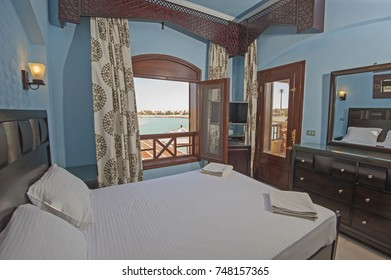 Interior design decor furnishing of luxury show home bedroom with furniture and sea view window